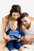 Caucasian parents and toddler son reading book in bed.