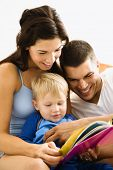 Caucasian parents and toddler son reading book.