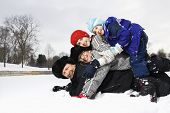 Portrait of happy Caucasian family of four lying stacked on top of each other in snow smiling at viewer.