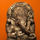 Statue of Hindu elephant Ganesha against orange wall.