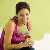 Pretty smiling woman kneeling in front of partially painted wall holding paintbrush.