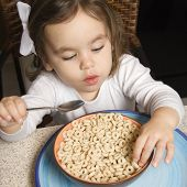 Caucasian girl eating bowl of cereal.