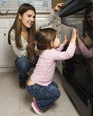 Caucasian mother and daughter kneeling by oven peering in.