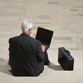 Back view of Caucasian middle aged businessman sitting on steps outdoors with laptop and briefcase.