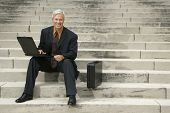 Caucasian middle aged businessman sitting on steps outdoors with laptop and briefcase smiling at vie