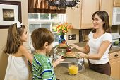 Hispanic mother giving healthy breakfast to young children in home kitchen.