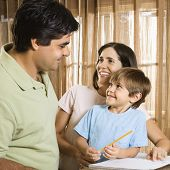 Hispanic parents making eye contact with son doing homework.