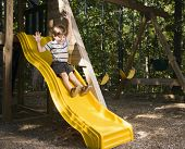 Hispanic boy sliding down outdoor slide with arms raised above head.