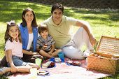 Hispanic family picnicing in the park and smiling at viewer.