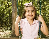 Hispanic girl sitting on playground swing smiling at viewer.