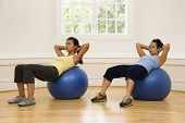 Two young women doing ab workout on balance balls.