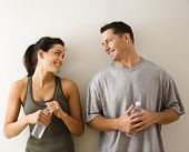 Man and woman at gym in fitness attire holding water bottles standing against wall smiling at eachot