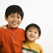 Portrait of young Asian brothers with arms around eachother smiling.