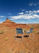 Two outdoor lawn chairs in scenic desert landscape with mesa land formation.