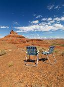 Dos sillas de jardín al aire libre en el pintoresco paisaje desértico con mesa formación de la tierra.