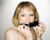 Portrait junge blonde caucasian Frau, die ihr Handy wütend beißt.