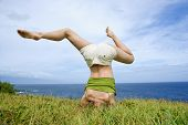Young woman doing headstand with legs askew in grass near ocean in Maui, Hawaii.