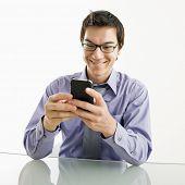 Sorridente empresário asiático sentado em mensagens de texto de mesa usando seu celular pda.