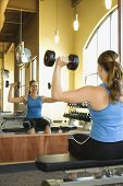Woman sitting on a weightlifting bench. She is looking in a mirror while lifting dumbbells. Vertical shot.
