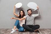 Photo of smiling handsome man with his wife sitting isolated over grey wall background. Looking came poster