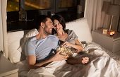people, family and leisure concept - couple with popcorn watching tv at night at home poster