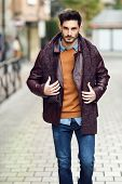 Attractive Young Man Walking In An Urban Road In Winter Clothes. poster