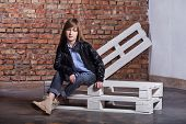 Girl Loft Interior.fashion Teen Girl. Stylish Mode Girl Sitting Pallets In Loft Interior. Girl Teen  poster