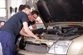 Man and woman team of mechanics using digital tablet while diagnosing car engine.