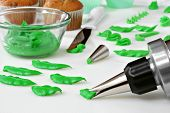 Green cake frosting being dispensed from decorator tip to form leaves.  Bowl of frosting and cupcake