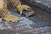 Builder Laying Blue Paving Bricks