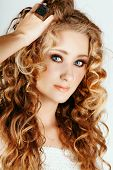 pic of strawberry blonde  - beautiful strawberry blond woman with blue eyes and long big curly hair with hand in hair - JPG