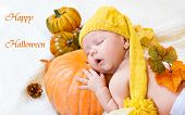 Happy Halloween greeting card with baby sleeping on a pumpkin
