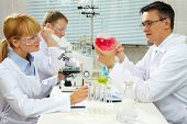 Group of clinicians studying new substance in laboratory poster