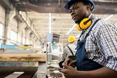 Concentrated African American Worker Wearing Overall And Hardhat Operating Machine With Help Of Digi poster