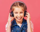 Cheerful girl listening to music with wireless headphones on bright pink background poster