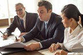 Content Business Man And Woman Looking At Serious Partner Signing Document. Three Business People Cl poster