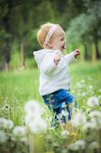 stock photo of defloration  - Outdoor portrait of a cute little baby in the grass - JPG