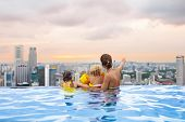 Family Swimming In Roof Top Outdoor Pool On Family Vacation In Singapore. City Skyline From Infinity poster