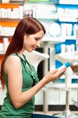 customer in a pharmacy or drugstore is looking for products