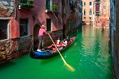 Gondolier Carries Tourists On Traditional Gondola On A Picturesque Venetian Canal In Sunny Day, Veni poster