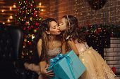 Family Celebrates Christmas. Happy Mother With Daughter In Magic Night. Sharing Christmas Presents O poster