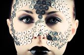 Conceptual shot of a woman with metal buttons on her face.