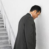 Hispanic businessman leaning head on wall