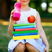 Happy Adorable Little Kid Girl Reading Book And Holding Different Colorful Books, Apples And Water B poster