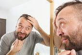 Happy Adult Man Looking At Hair In Mirror poster