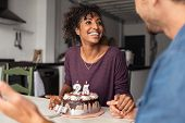 Multiethnic couple sitting at table and celebrating birthday at home. Young african girl surprised o poster