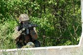 picture of hider  - The soldier in protective clothes with weapon - JPG