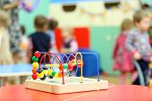 Colorful wooden toy stand at table in kindergarten; children play