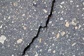 Vertical Broken Crack On The Surface Of Asphalt Pavement. The Crack Is Diagonal And Bisects. Gray As poster