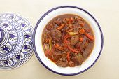A moroccan beef tagine served in the traditional tagine dish, from above. The casserole uses beef, onion, carrots, capsicums, a cinnamon stick and a traditional mix of spices known as ras el hanout
